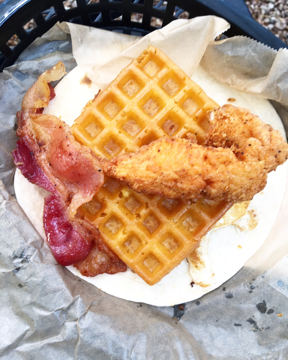 THE ROSCOE -A CRISP WAFFLE, FRIED EGG, FRIED CHICKEN, AND A SLICE OF BACON.SERVED WITH A SIDE OF MAPLE SYRUP ON A FLOUR TORTILLA.
