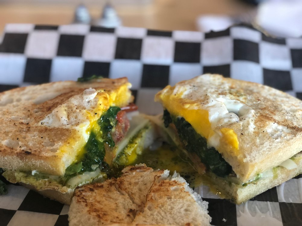 LIL' Stacker: Egg in a hole sandwich, sautéed spinach, pesto, red onion, roasted tomato, choice of swiss or provolone