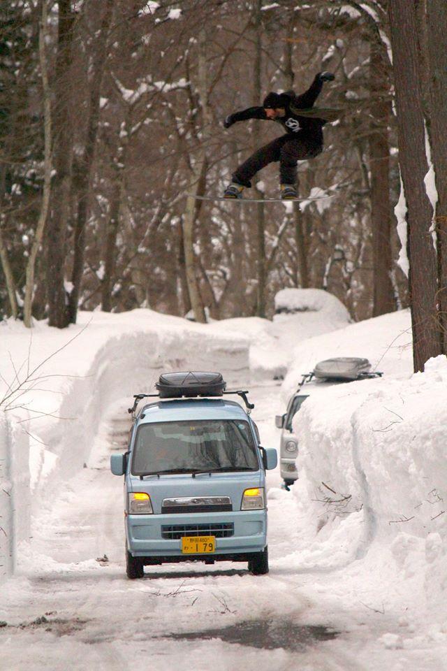Snowboarder jumps over Japan Camper Van