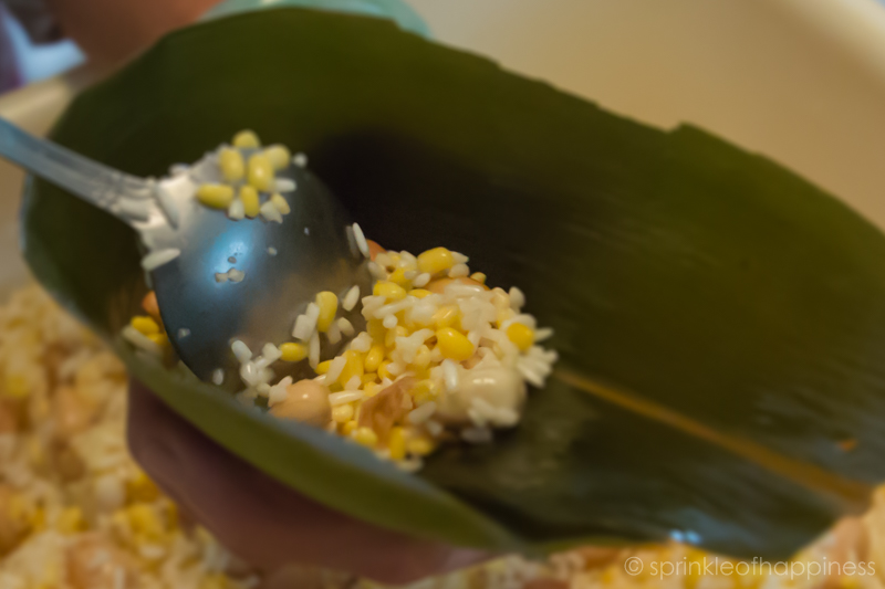 First step of wrapping joong or zongzi. Take a bamboo leaf and fold it into a cone shape. Spoon in glutinous rice mixed with peanuts and mung beans.
