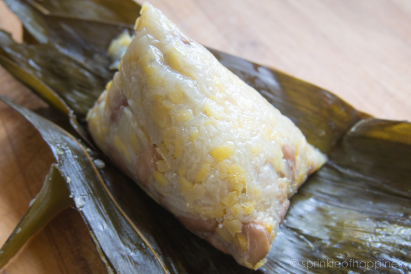 Untie twine and unwrap bamboo leaf to reveal a simple package of sticky glutinous rice. Joong Zongzi
