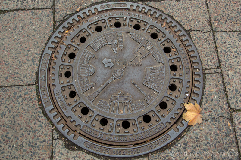 Berlin manhole cover with main attractions on it - Berlin TV Tower, Brandenburg Gate, Reichstag, Marienkirche, Olympia Stadium, Victory Column