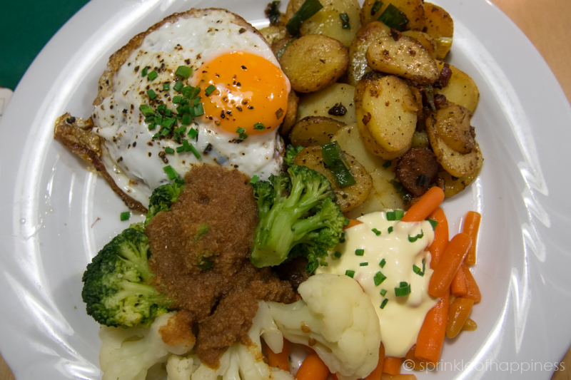 Gasthaus Julchen Hoppe - Homemade meatball with fried egg, cauliflower, broccoli, carrots and brown butter with crispy fried potato