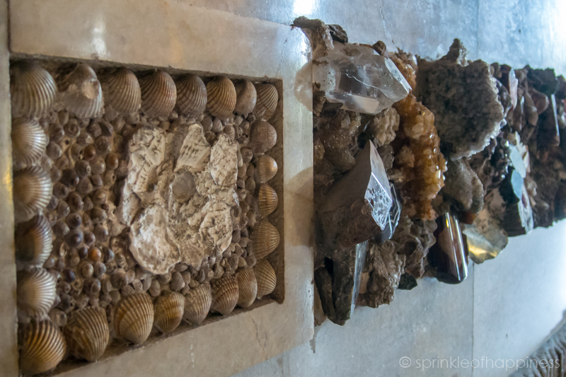 Grotto Hall - seashell, rocks and fossil placed on marble wall