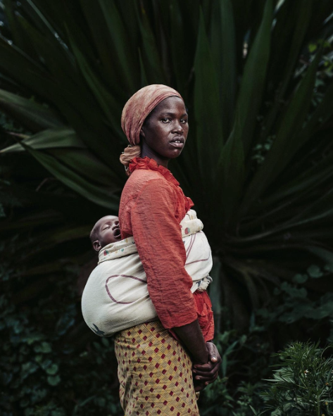 A single mother in Rwanda walks through a farm with her baby.