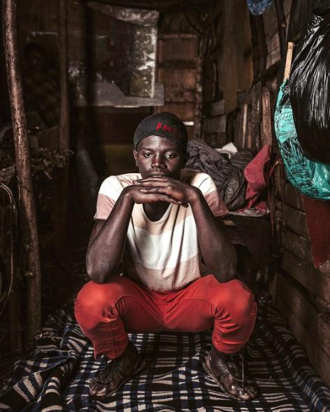 A teenager sits on his bed in Nairobi, Kenya.