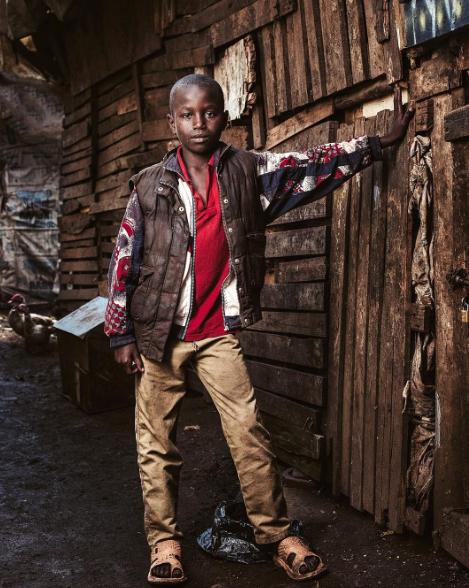 A young boy poses next to his front door in Nairobi, Kenya.