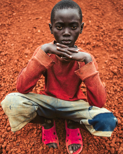 A young boy in Rwanda poses on a pile of dirt.