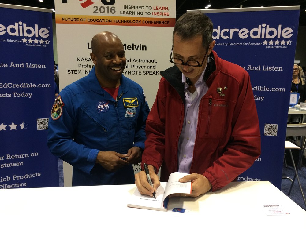 Signing 'Astronaut Instruction Manual' for astronaut Leland Melvin