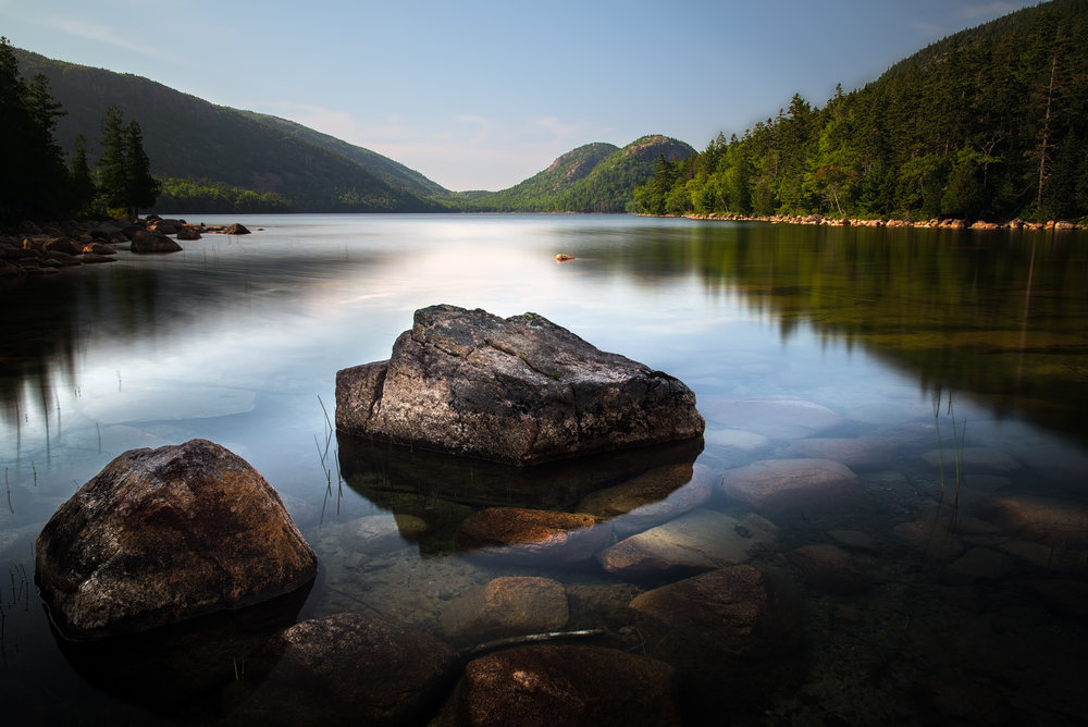 Humid, Hazy clear blue skies for most of the afternoon but things started to change during the late afternoon.  This is a final shot before getting some dinner.  Clouds are starting to move in as the Sun lights up the distant trees and illuminate the Bubbles.  A peaceful moment to contemplate ones place in the Universe.  - Acadia National Park.  Camera: Nikon D750 Lens: 24.0-120.0 mm f/4.0 @ ƒ/11.0 Focal Length: 27.0 mm Shutter Speed: 20 secs ISO: 50  Polarizer to cut through the reflections.  Two images used, one non long exposure for the distant trees, focus on the bubbles.  The other long exposure for the lower section, focus on the near rocks.  Images blended in Photoshop.