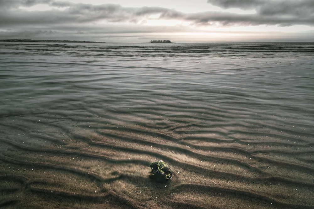 An old crusty eye bolt lies buried in the sand just beneath the surface of the water. Though no rope exists between the two, Charles Island seems anchored in the scene.