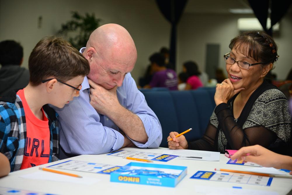Josiah Roberts actively engaged in a game of math bingo with parents Jerry and Nellie Joy.