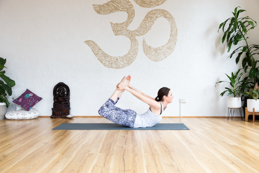 Bow pose. 5-9x Balance on navel. Shoulders back. Engage butt and core muscles.