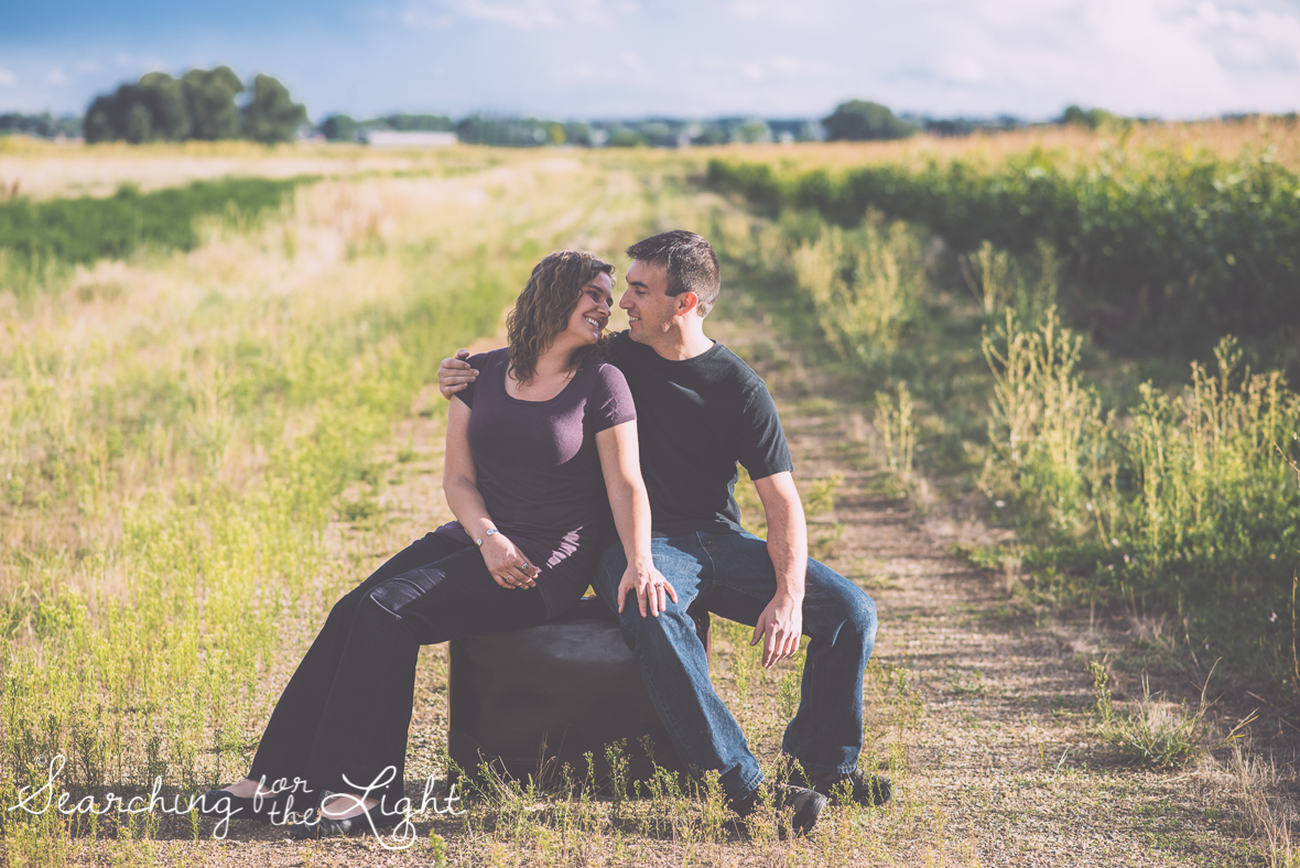colorado wedding photographer field engagement session featuring suitcases