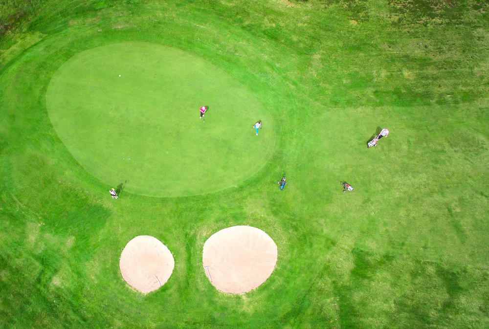 Boat of Garten golf course birds eye view of 7th hole as golfers play.
