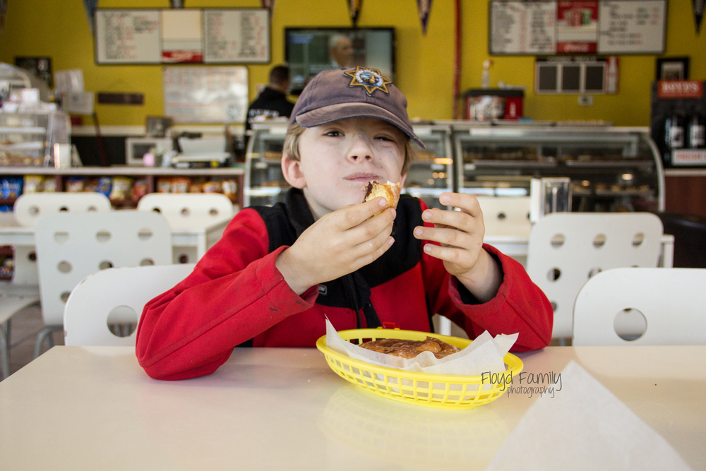 boy eating donut in donut shop | Placerville-Children-Photographer