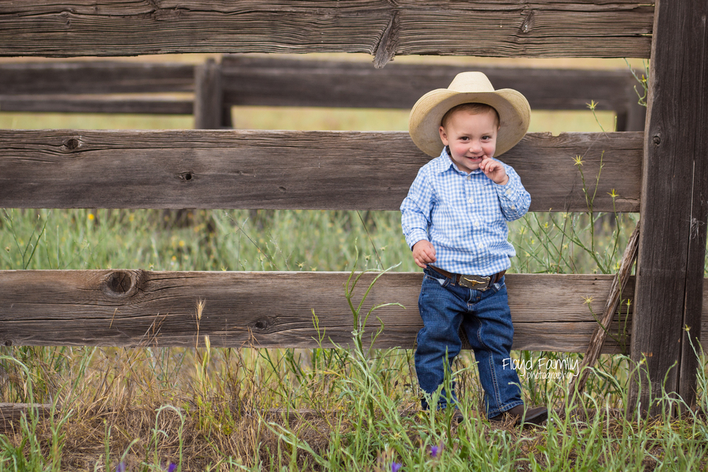 Toddler boy standing on the side of wood fence | Placerville Documentary Family Photography