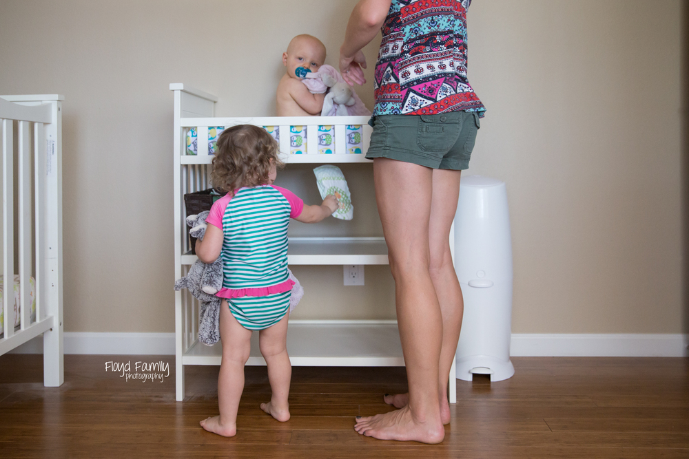 big sister helping mom change little sister's diaper |