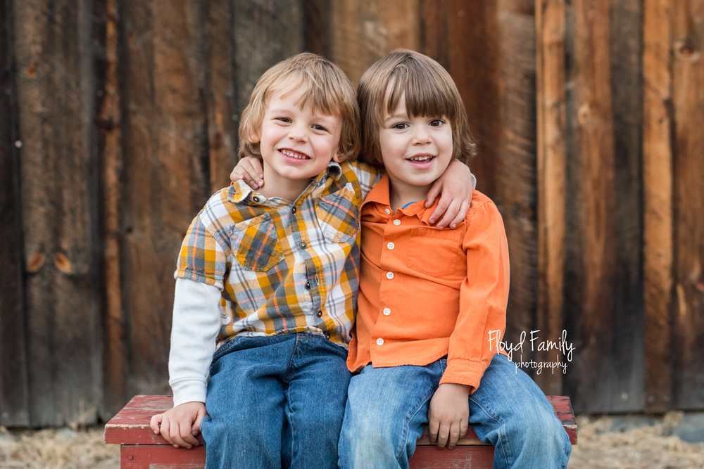 two cute boys sitting together on bench in front of barn