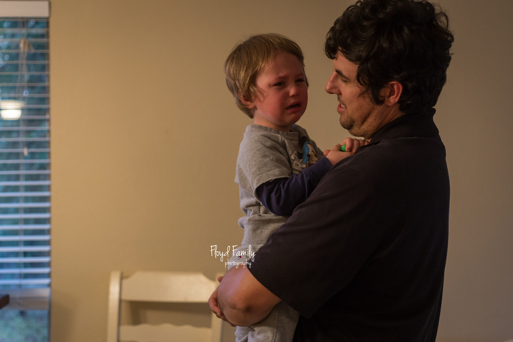 little boy being held by dad while he cries