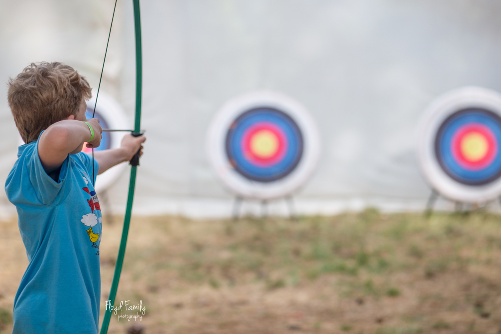 Boy practicing archery at cub scout camp