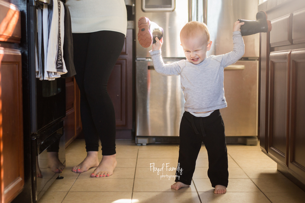 boy holding rain boots in the kitchen while mom cooks