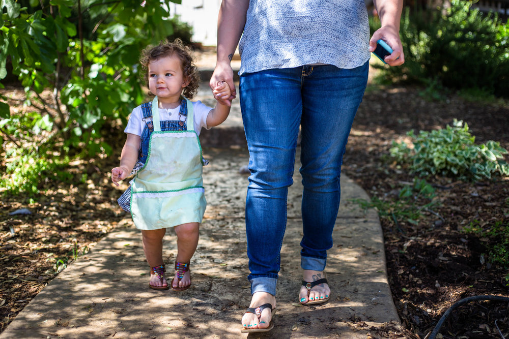 Little girl and mom walking down sidewalk of home outside in the shade