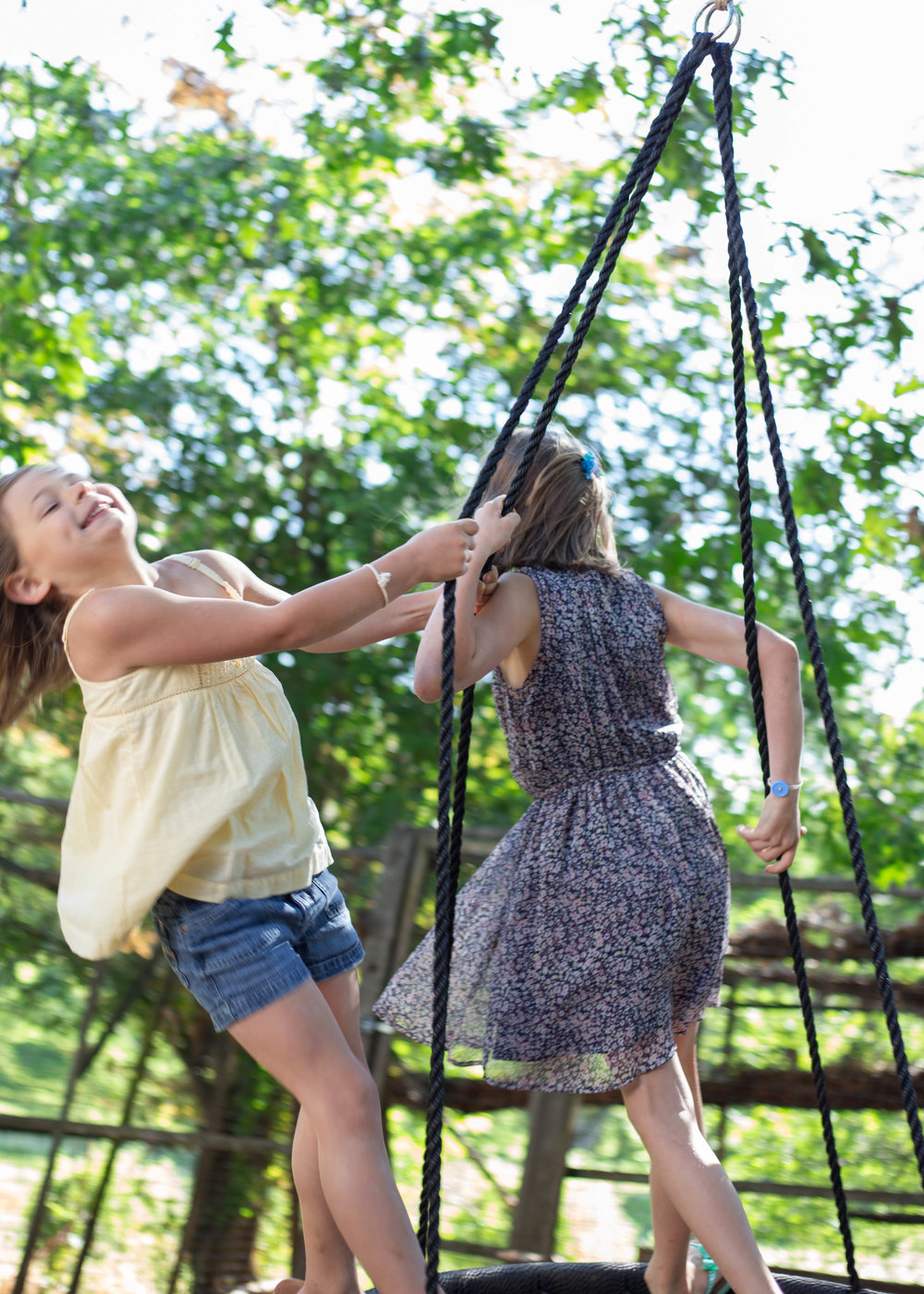Two young sisters swinging on the tire swing outside their home under the trees
