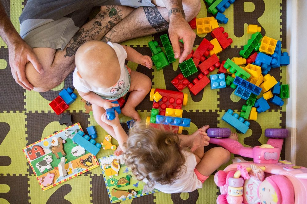 Two little girls playing with large lego blocks