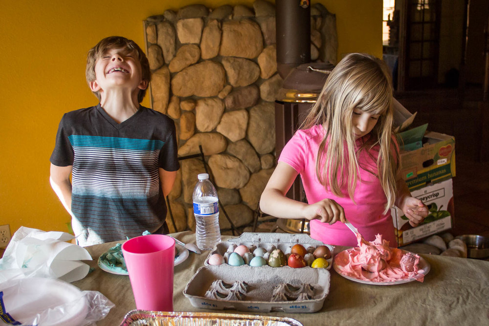 Two kids dying eggs for Easter