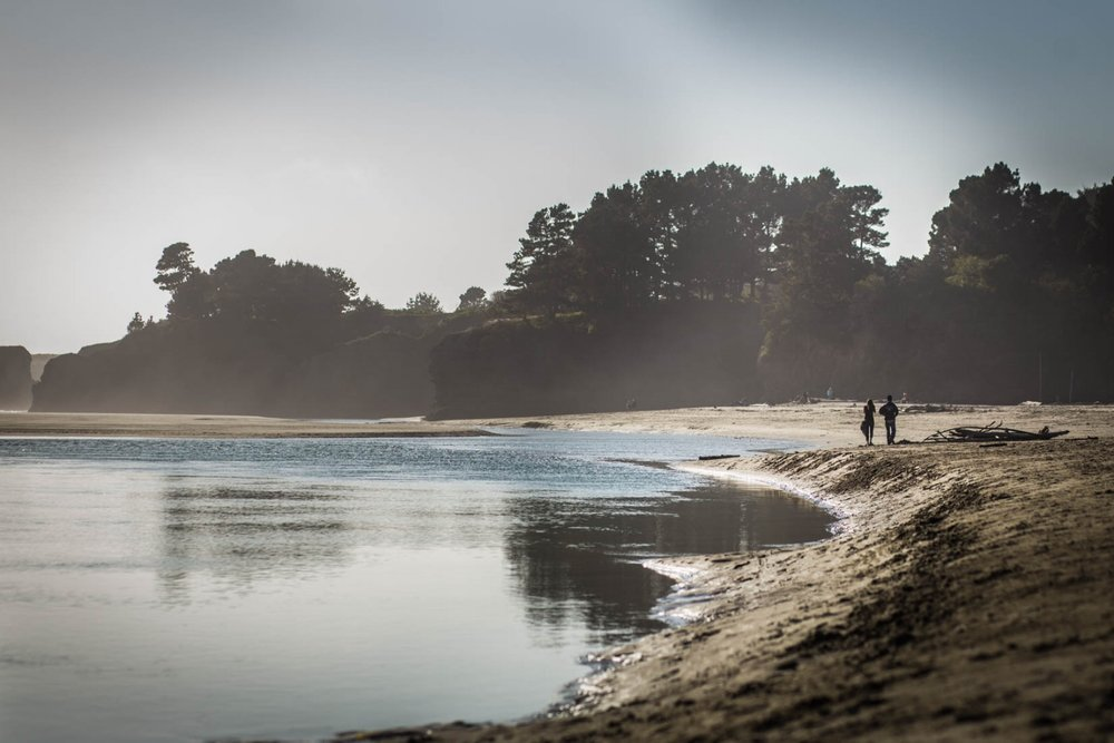 Two people walking on the beach in Mendocino on a cold day