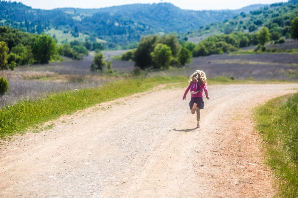 Girl running on her own on a hiking trip gold country