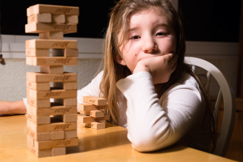 Little girl sitting at table with chin on hand in table lamp light playing Jenga | Photos El Dorado Hills Family
