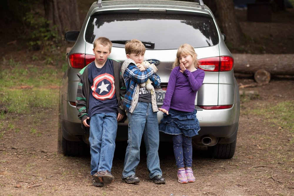 Three kids standing behind a car while on a camping trip