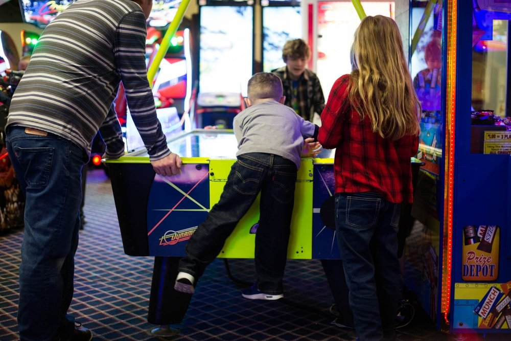Four kids playing air hockey at the arcade