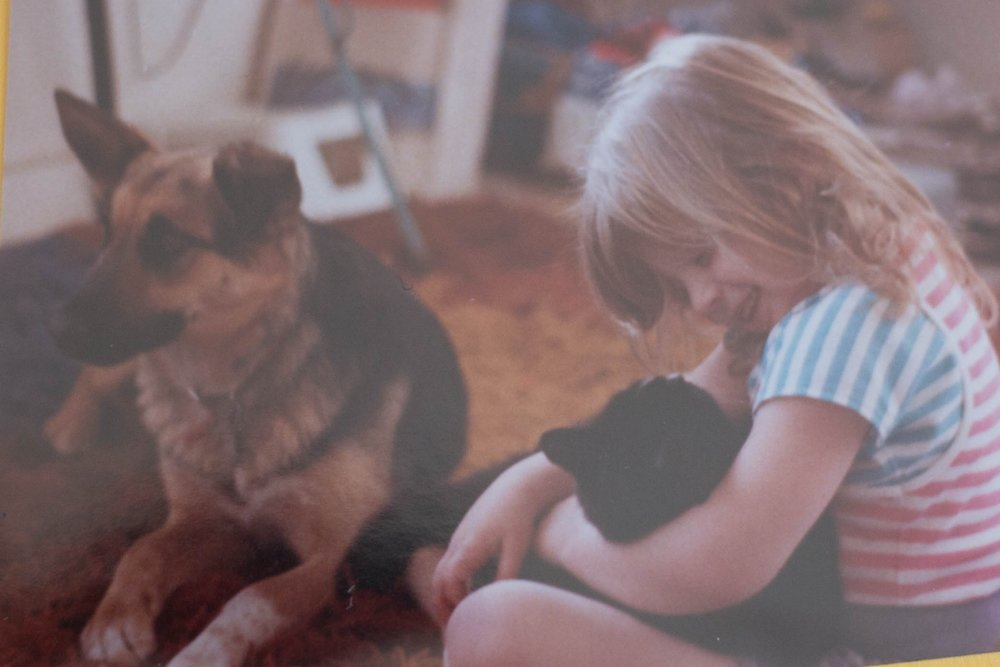 Little girl sitting with her cat and her dog on the floor smiling.