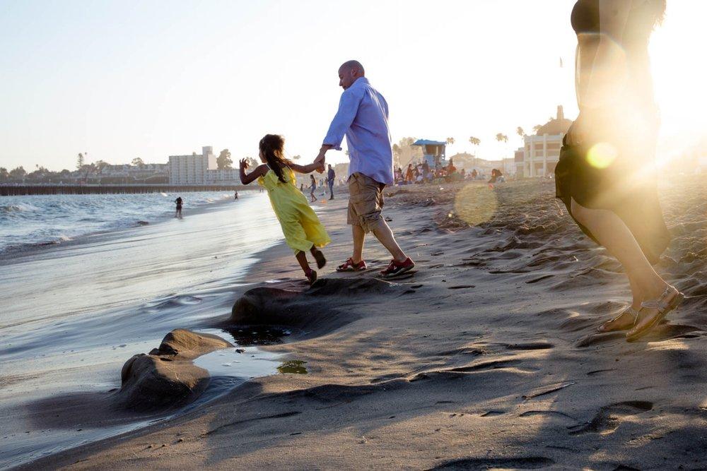 Daughter pulling dad towards the ocean water on the Santa Cruz Beach Boardwalk
