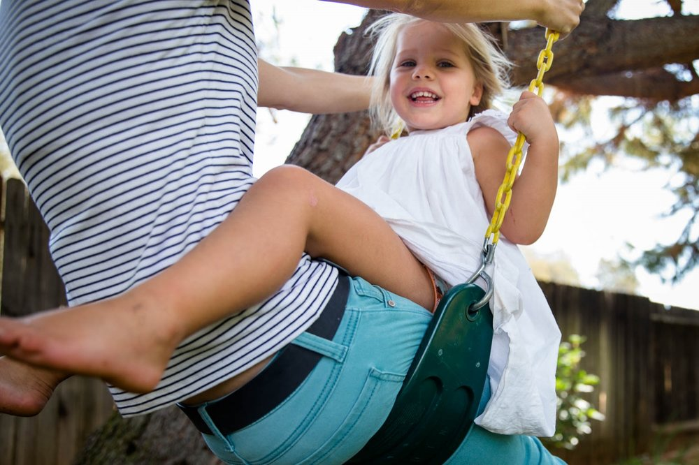 Swinging on the swing with mom and smiling