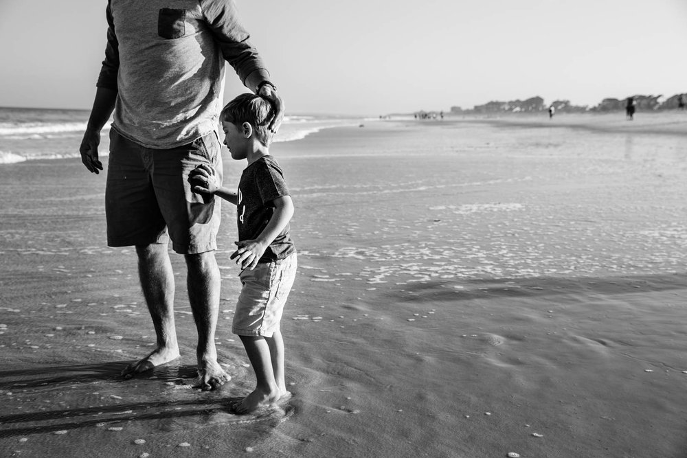 Little boy standing with dad at the beach while he lovingly caresses his son