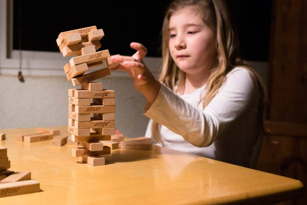 Little girl playing Jenga at the dining room table