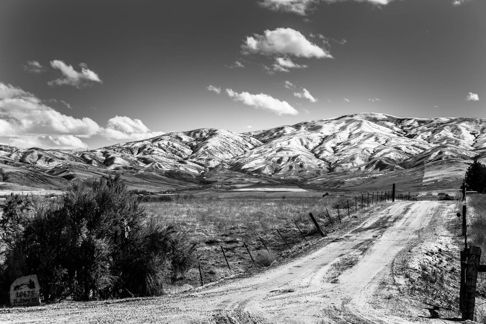 long dirt road landscape image of boise foothills in black and white with puffy coouds