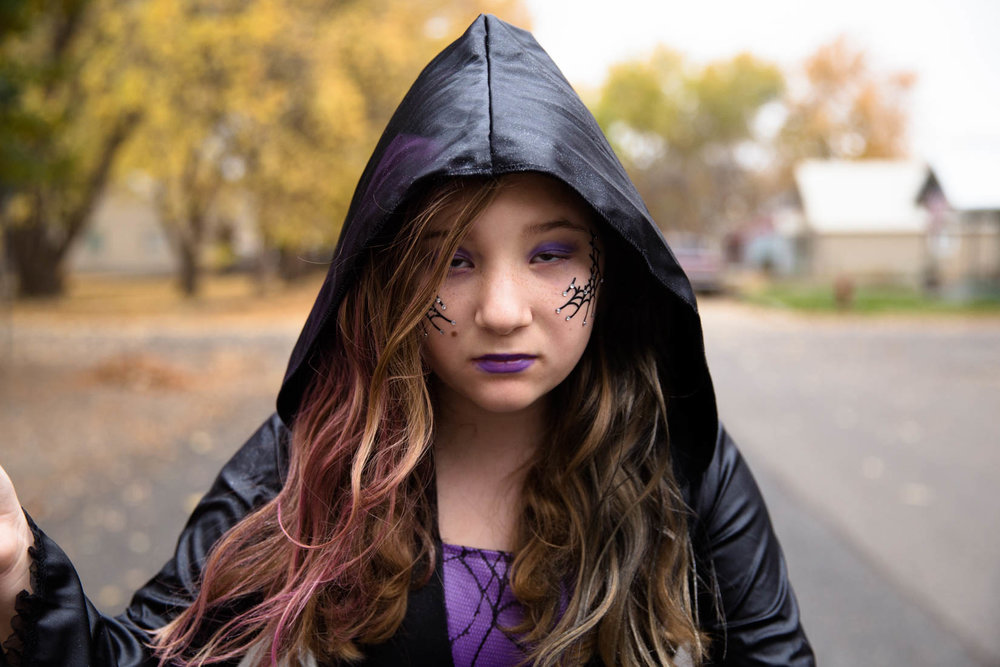 young girl on Halloween dressed as a witch and standing in the middle of the street.