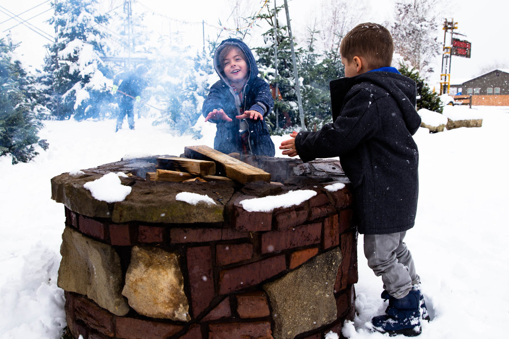Two kids standing by the fire at the Christmas tree lot warming their hands.