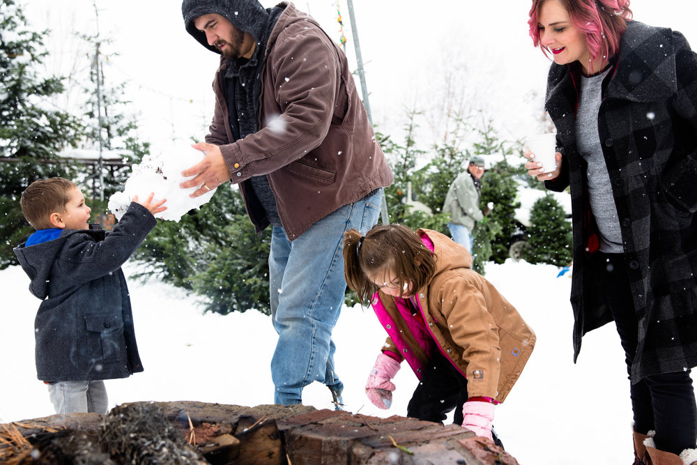 Two parents and two kids playing in the snow by the campfire while hunting for their Christmas Tree