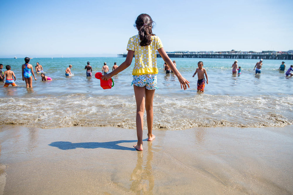 Young girl walking into the ocean with a bucket to grab water on the beach with lots of people behind her.
