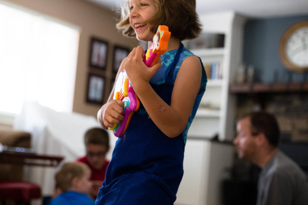 Young girl playing a toy guitar while her family sits behind her in the living room