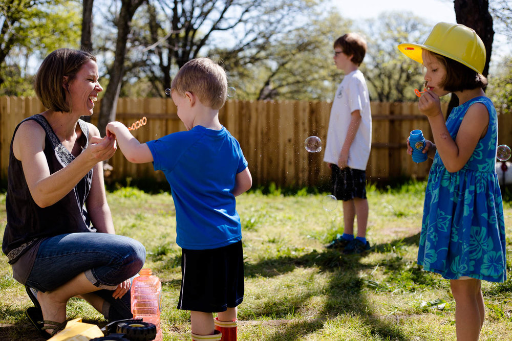 Mom laughing while kids play with bubbles in the back yard