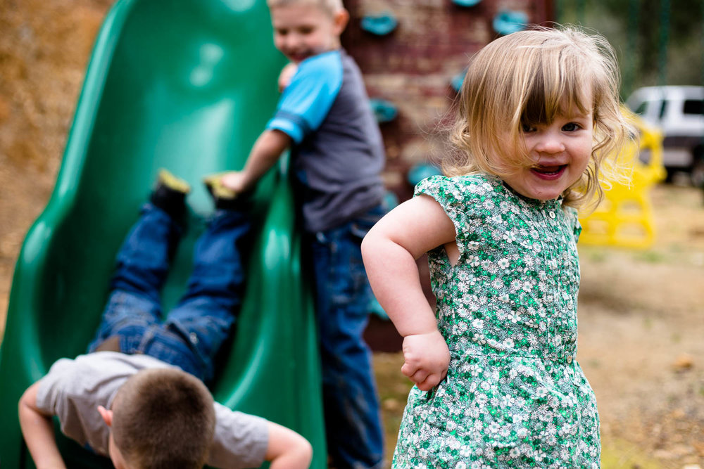 Little girl laughing as she just got off the slide and brothers are behind her going down slide
