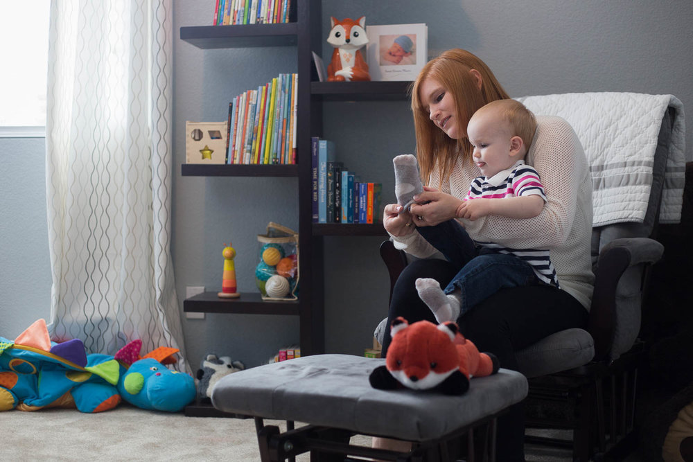Mom sitting on rocking chair with toddler son in lap putting on his socks for him