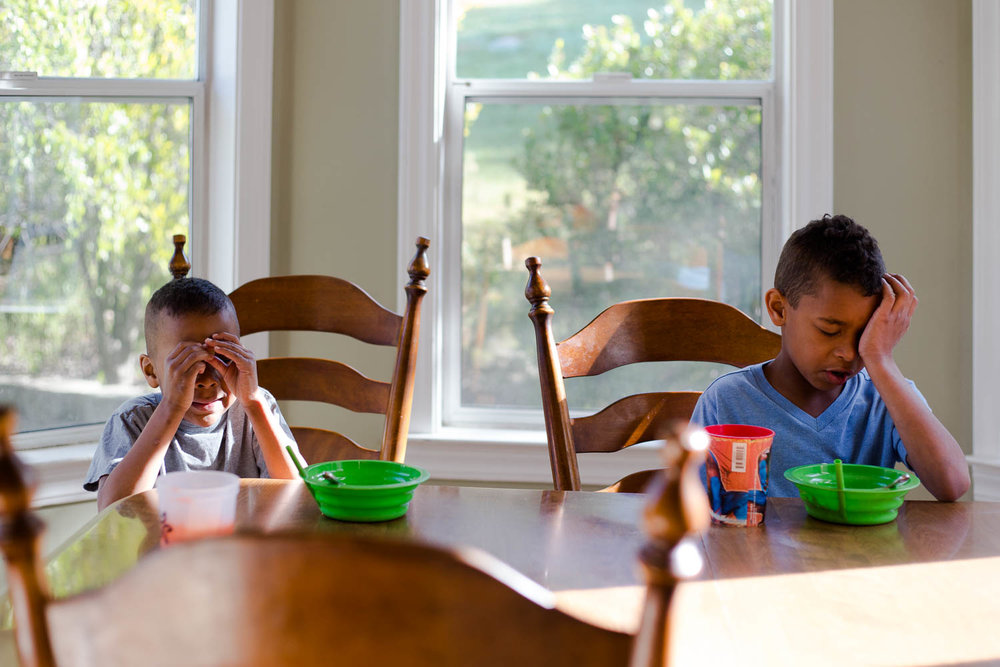Two boys sitting at dining room table while eating breakfast and rubbing their eyes